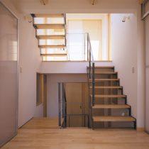 シェアードハウスのリビングよりトップライトからの光が差し込む階段室を見る