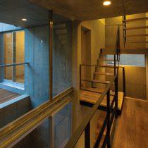 階段室の上部へのボイドとアプローチから庭へと抜けるボイドを見る