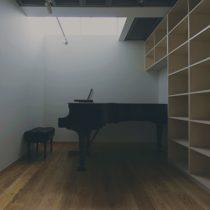 北側のハイサイドライトから天空光が差し込むピアノ室を見る