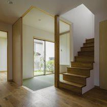 玄関から階段と和室越しに庭を見る