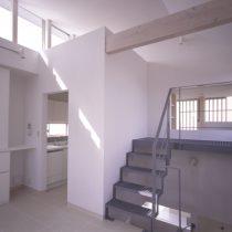 ハイサイドライトより光が差し込むリビングから階段室とキッチン方向を見る